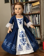 A 18-inch doll in a colonial formal decorated with embroidery