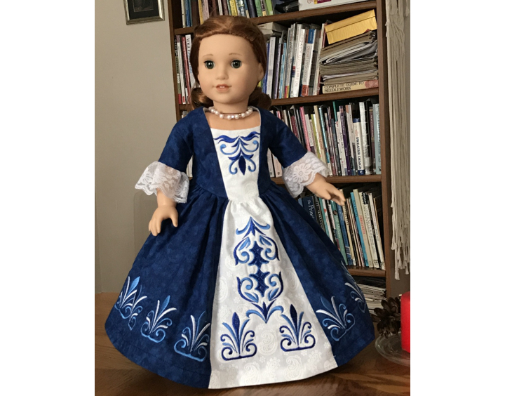 Photo of a 18-inch doll modelling the formal colonial dress decorated with the machine embroidery