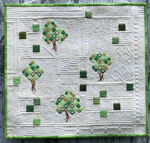 Small white quilt with green trees embroidery