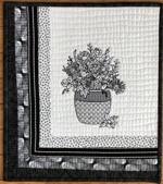 Wall quilt with black-and-white borders, white central part and black flower embroidery on it.