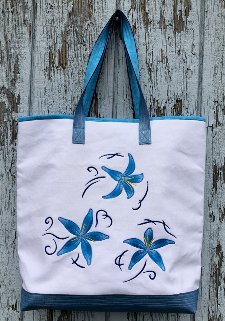 Finished white canvas bag with blue lilies embroidery.