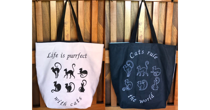FInished tote , one panel is white with black embroidery, another is black with white embroidery.