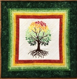 Small quilt with multicolored borders which match the folliage of the embroidered tree.