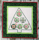 Small quilt with Christmas ornaments composed into a shape of a Christmas tree.