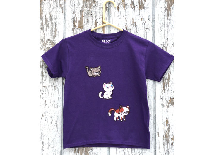 A kid's t-shirt decorated with kitten embroidery