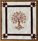 Small wall quilt with fall tree embroidery.