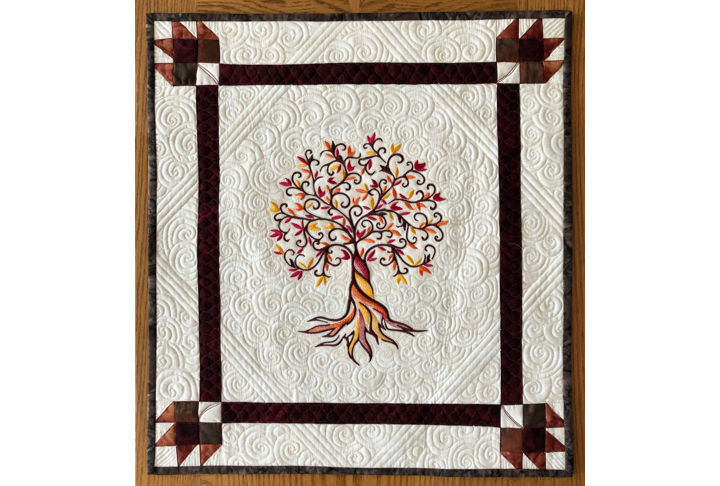 Small wall quilt with autumn tree embroidery.