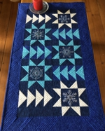 Quilted Tablerunner with pieced stars and embroidery.