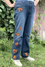 A pair of nlue jeans decorated with fall leaves embroidery