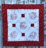 Red-and-white wall quilt with bird embroidery