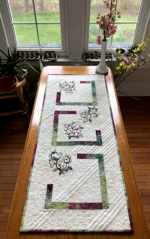 Quilted tablerunner with spring vines embroidery.