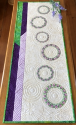 Quilted tabletopper with flower wreaths embroidery