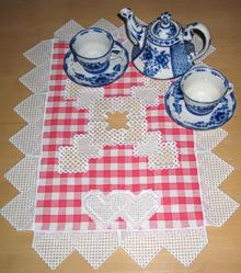 A table topper desorated with the faux hardanger machine embroidery.