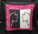 Black and pink pillow with black and white embroidered center. Embroidery design is cat silhouettes.