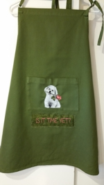 A green apron with the embroidery of a puppy on its pocket.